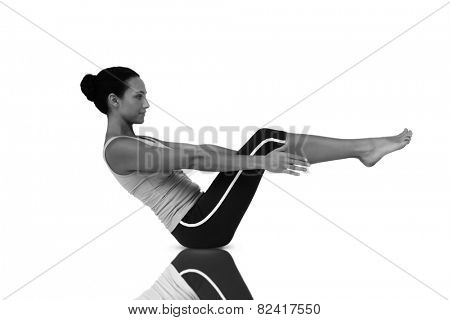 Side view of a fit young woman doing the boat pose against mirror