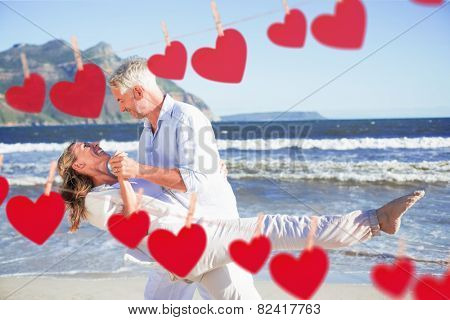 Happy couple dancing on the beach together against hearts hanging on a line
