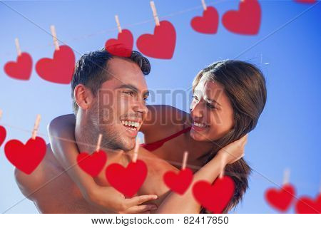 Handsome man carrying his girlfriend on his back against hearts hanging on a line