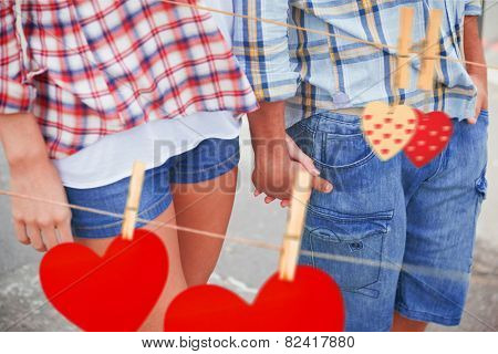 Couple in check shirts and denim holding hands against hearts hanging on the line
