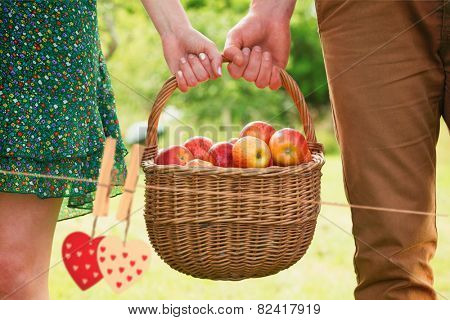 Basket of apples being carried by a young couple against hearts hanging on the line