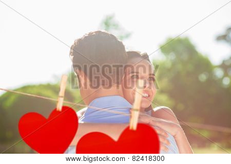 Loving and happy woman embracing man at park against hearts hanging on a line