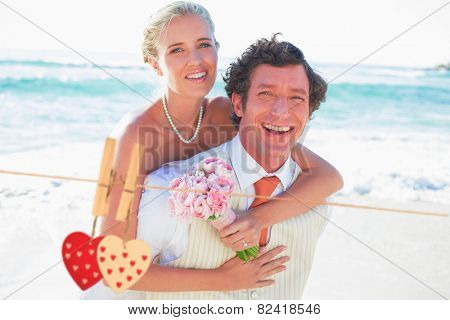 Handsome groom giving his new wife a piggy back against hearts hanging on the line