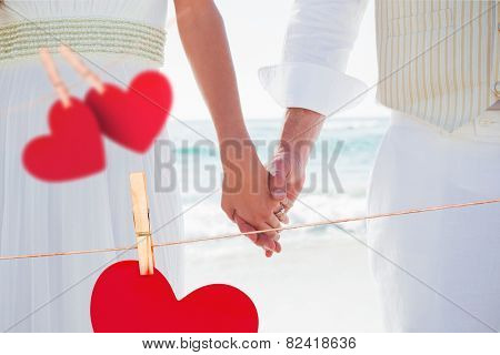 Newlyweds holding hands against hearts hanging on a line