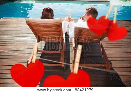 Couple toasting champagne by swimming pool against hearts hanging on a line