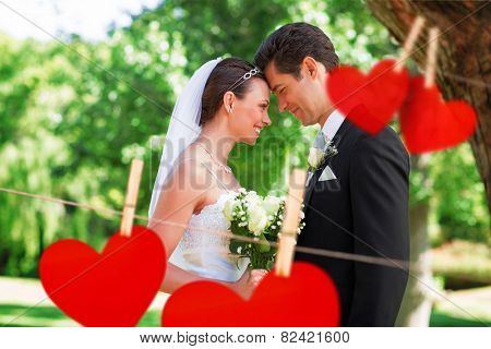 Loving newly wed couple in garden against hearts hanging on a line