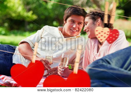 Man smiling as he looks at his friend during a picnic against hearts hanging on the line