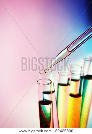 Pipette adding fluid to the one of test-tubes on bright background