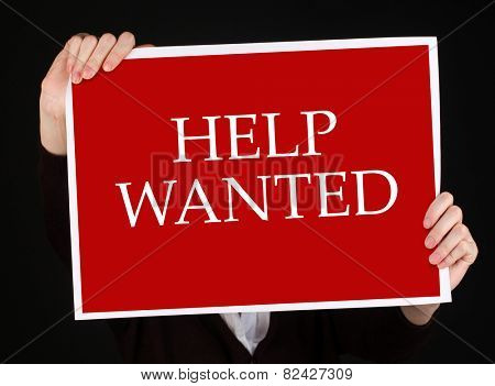 Young businesswoman holding poster with Help Wanted text on it