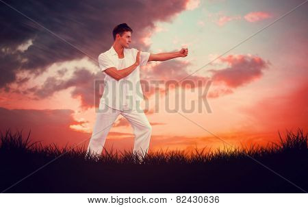 Handsome man in white doing tai chi against red sky over grass