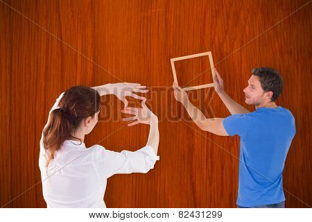 Couple deciding to hang picture against wooden oak table