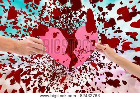 Hands holding two halves of broken heart against digitally generated pink and blue girly design
