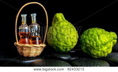 Aromatic Spa Concept Of Bergamot Fruits And  Bottles Essential Oil In Basket On Zen Basalt Black Sto