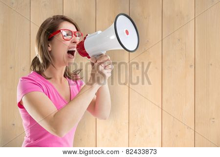 Angry woman with megaphone and glasses against wooden planks