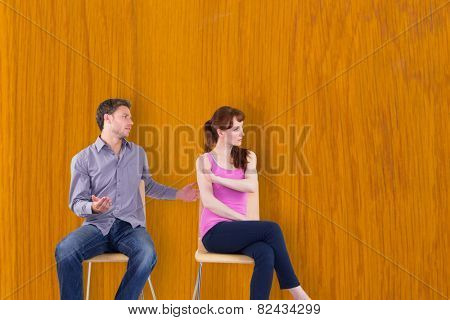 Sitting couple having an argument against wooden pine table