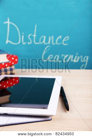Distance learning concept with tablet and books on blackboard background