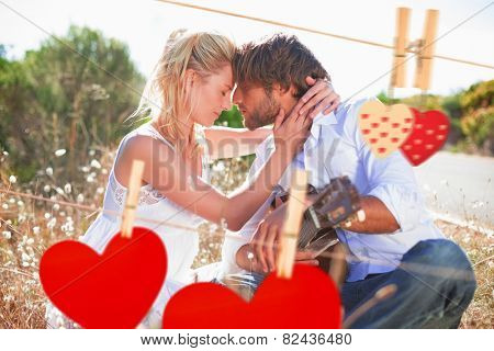 Handsome man serenading his girlfriend with guitar against hearts hanging on the line