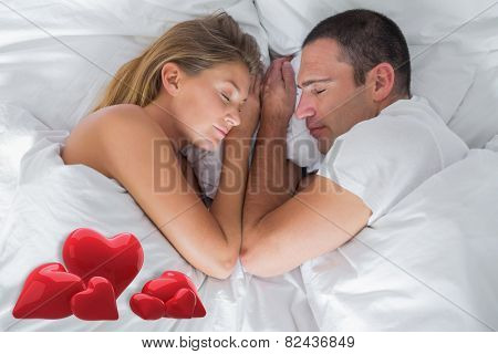 Cute couple lying asleep in bed against love hearts