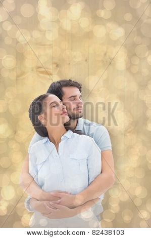 Cute couple embracing with eyes closed against light glowing dots design pattern