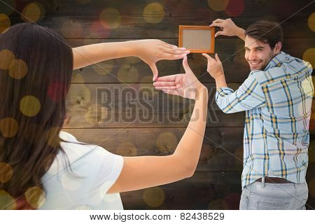 Happy young couple putting up picture frame against close up of christmas lights
