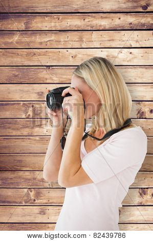 Happy blonde taking a photo on camera against wooden planks