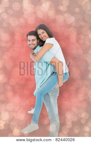 Happy casual man giving pretty girlfriend piggy back against light glowing dots design pattern