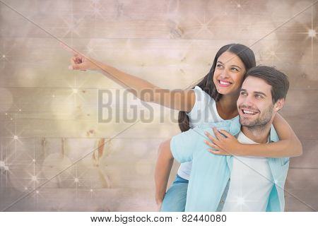 Happy casual man giving pretty girlfriend piggy back against shimmering light design on grey
