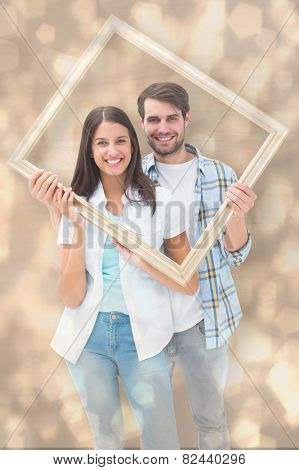 Happy young couple holding picture frame against light glowing dots design pattern