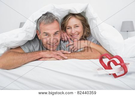 Cheerful couple under the duvet against linking hearts