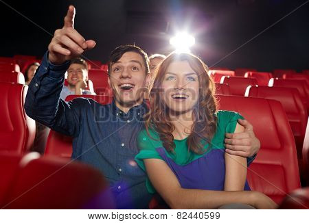 cinema, entertainment, gesture, emotions and people concept - happy friends watching movie pointing finger to screen in theater