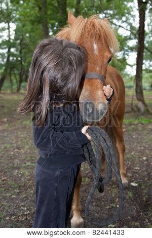 A Little Girl Kissing And Her Purebred Shetland Pony