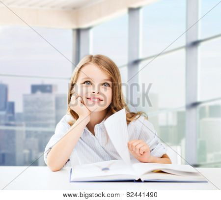 education, people, children and school concept - little student girl sitting at table with books and writing in notebook over classroom background