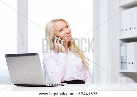 education, business, communication and technology concept - smiling businesswoman or student with laptop computer calling on smartphone in office