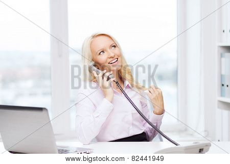 education, business, communication and technology concept - smiling businesswoman or student with laptop computer calling on phone in office