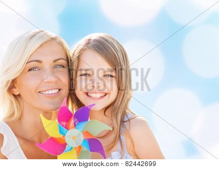 summer holidays, family, children and people concept - happy mother and girl with pinwheel toy over blue lights background
