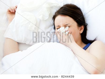 Sick Young Woman Using A Tissue Lying In A Bed