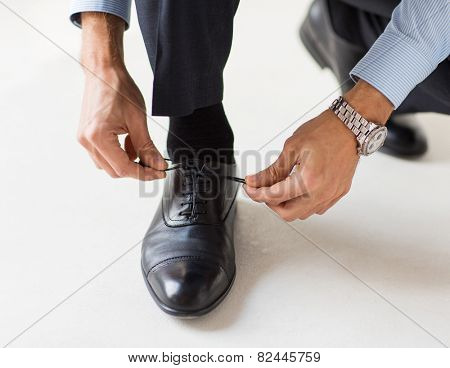 people, business, fashion and footwear concept - close up of man leg and hands tying shoe laces