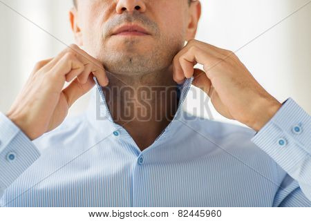 people, business, fashion and clothing concept - close up of man dressing up and adjusting shirt collar at home