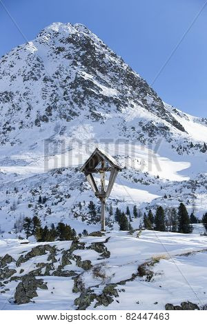 Cross In Snowy Mountain Landscape