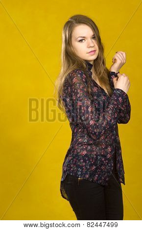 Woman Buttoning On The Sleeve. Yellow Background