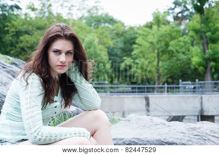 Portrait Of Young Brunette Sitting On The Bouders