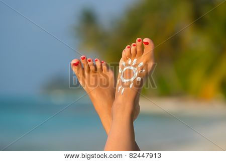 Woman Foot With Sun-shaped Sun Cream In The Tropical Beach Conceptual Image Of Vacation