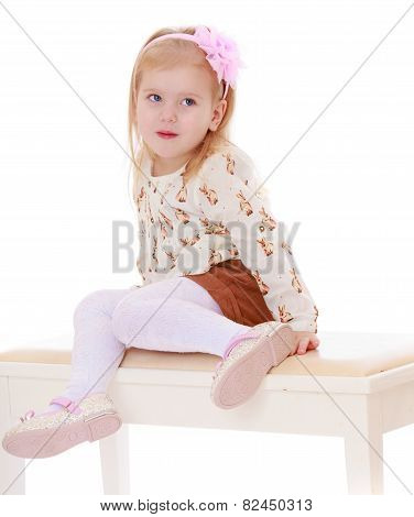 Beautiful little girl sitting on white banquettes.