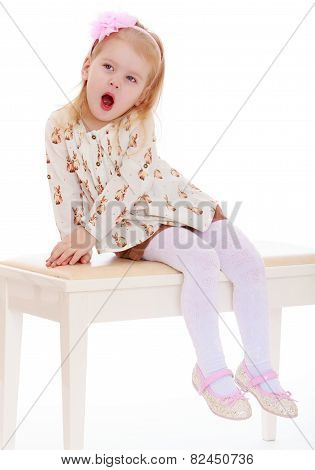 little girl yawns while sitting on the couch.