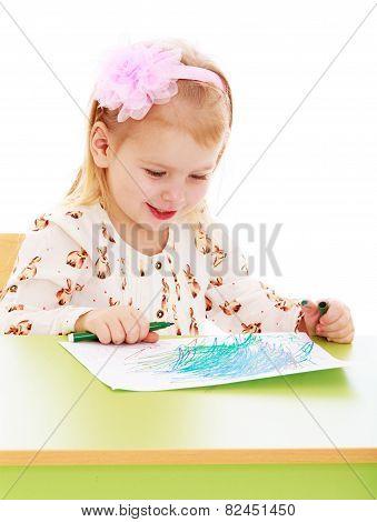 Very smart little girl draws sitting behind a desk.