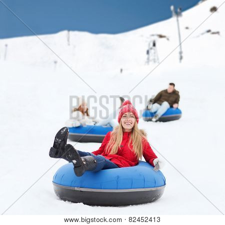 winter, leisure, sport, friendship and people concept - group of happy friends sliding down on snow tubes over mountain background