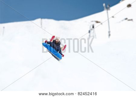 winter, leisure, sport, and people concept - happy teenage girl or woman sliding down on snow tube over mountain background
