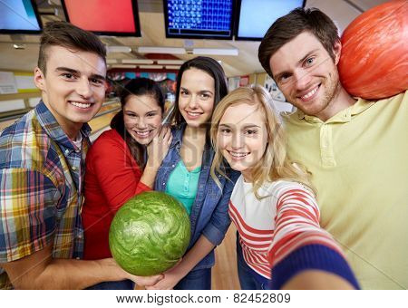 people, leisure, sport, friendship and entertainment concept - happy friends taking selfie with camera or smartphone in bowling club