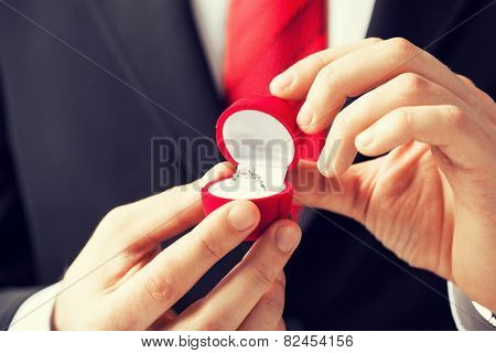 man making proposal with wedding ring and gift box.