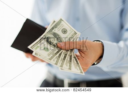 people, business, finances and money concept - close up of businessman hands holding open wallet with dollar cash